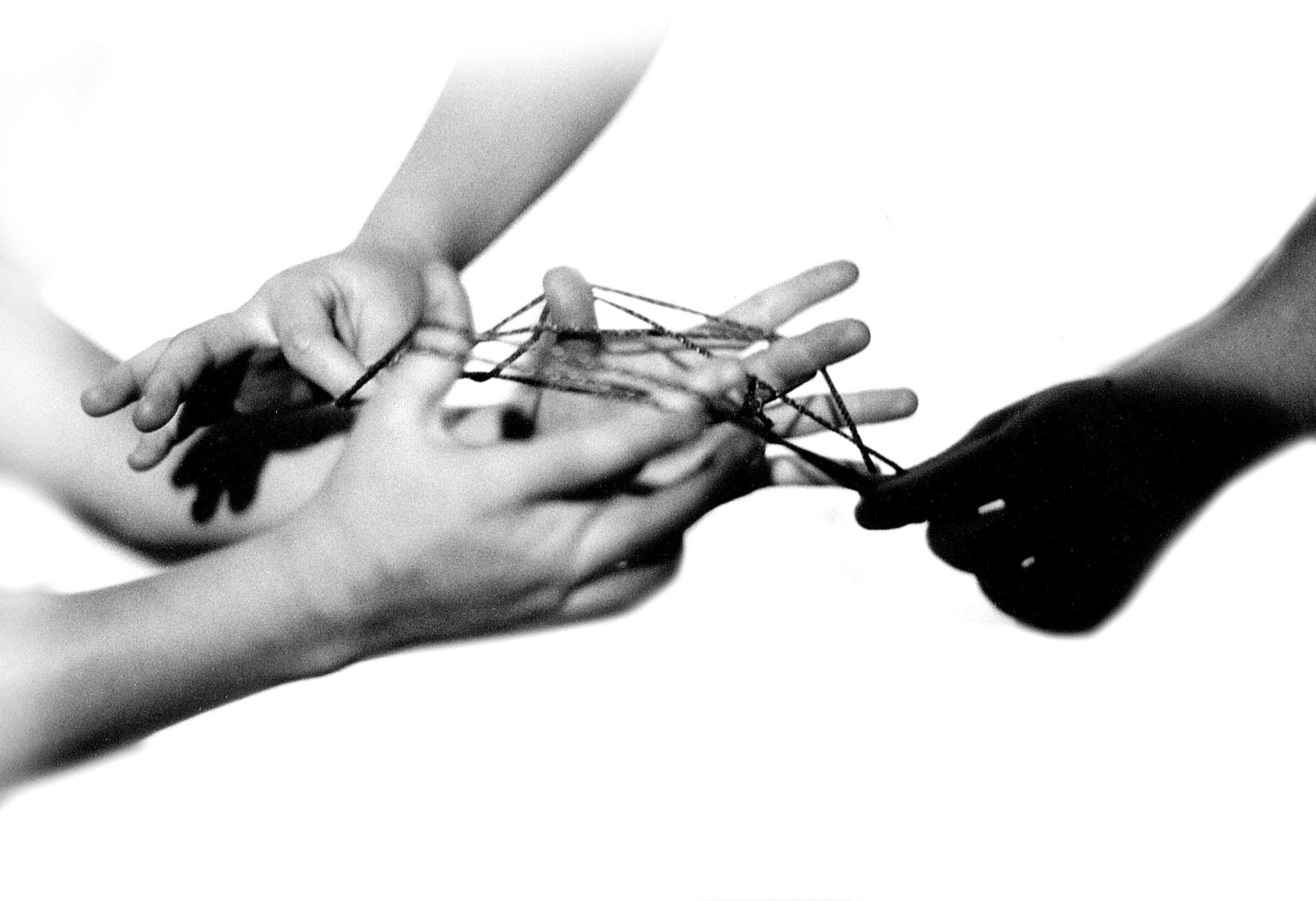 Hände, zwischen denen ein Faden gespannt ist