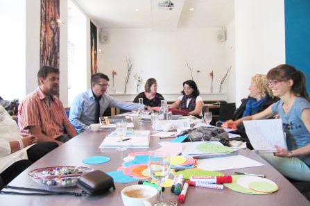Menschen sitzen am Tisch und entwickeln Konzepte für Wissensmanagement