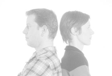 zwei Menschen stehen Rücken an Rücken